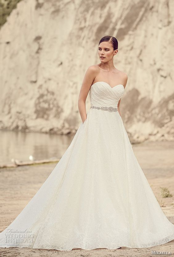 ruched strapless wedding dress with an embellished belt and pockets