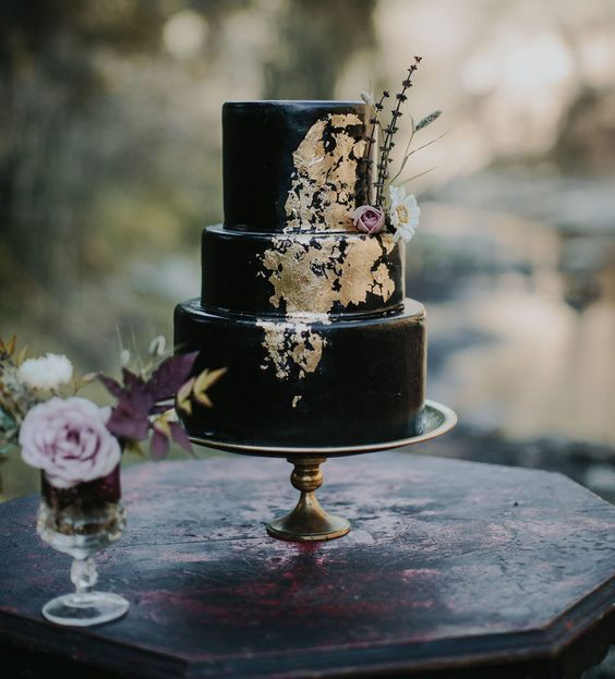 black iced wedding cake with gold detailing and fresh flowers
