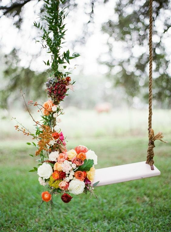 a swing decorated with lush fall-themed flowers and greenery