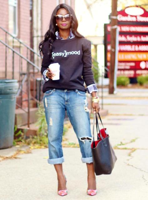 With distressed jeans, tote and printed sweatshirt