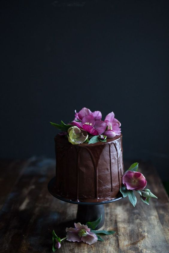 chocolate wedding cake with chocolate drip and pink blooms on top