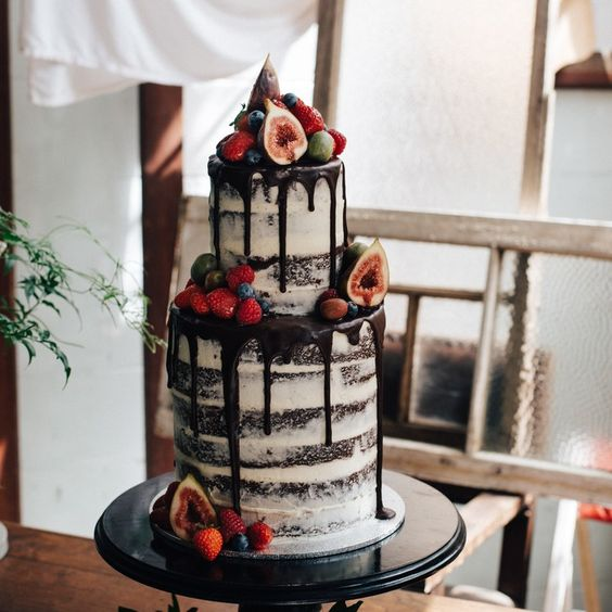 semi naked chocolate wedidng cake with chocolate drip, figs, raspberries and strawberries