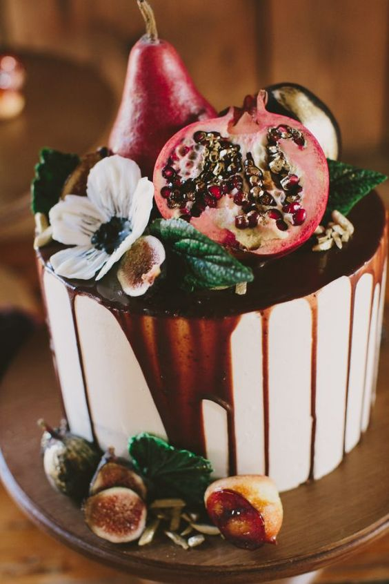 iced wedding cake with a pomegranate drip, with pomegranates, figs and pears