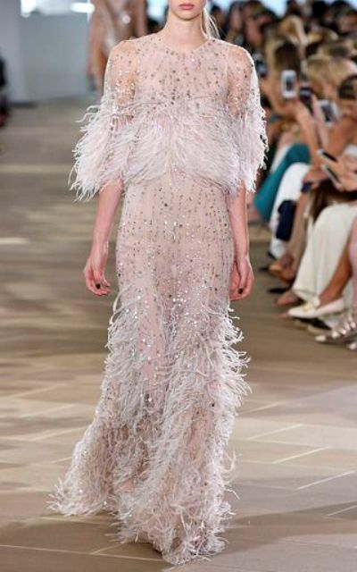 sparkling semi sheer wedding gown with crystals and a feather skirt, bodice and sleeves by Monique Lhuillier