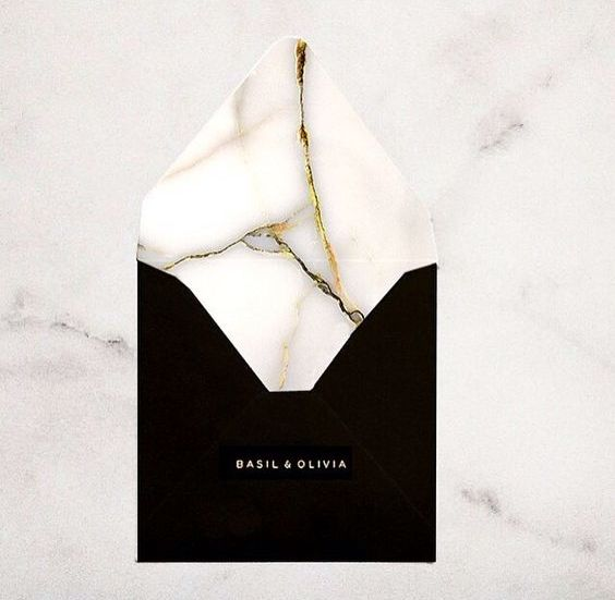 a black envelope with a marble lining with gold touches