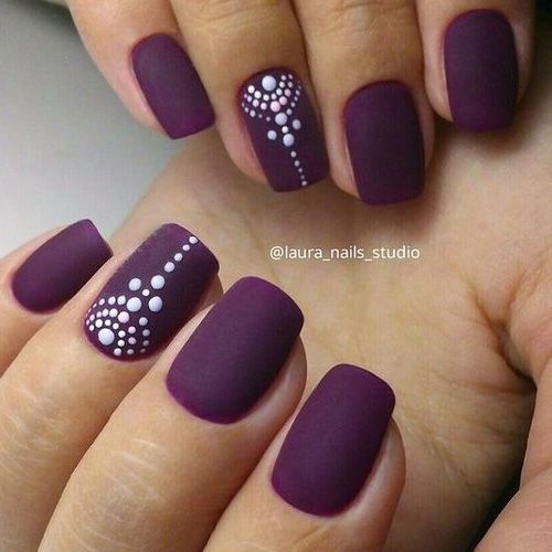 matte deep purple nails with accent ones with a tribal polka dot design