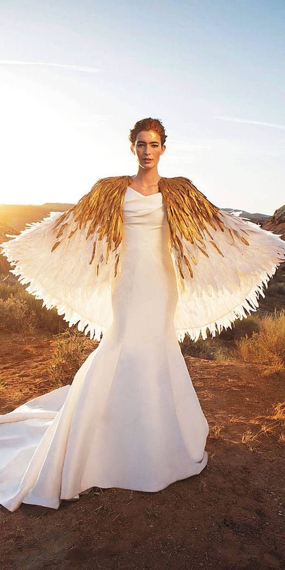 modern fit and flare wedding dress with a train and a white and gold feather cape attached