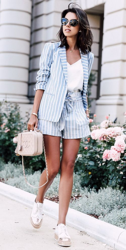 a blue striped shorts suit with a white V-neckline top and flat shoes