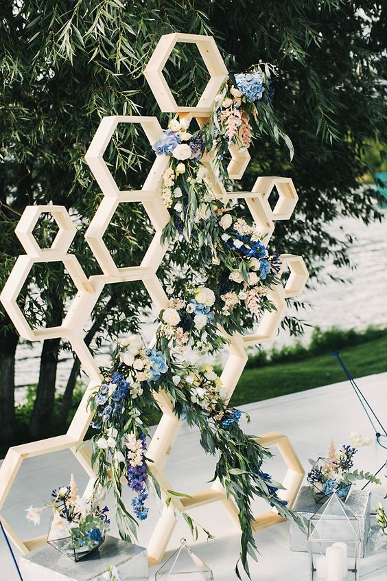 a honeycomb wedding backdrop decorated with lush greenery, neutral and blue flowers