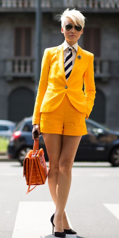 a bold yellow shorts suit with a striped shirt and tie and black pumps
