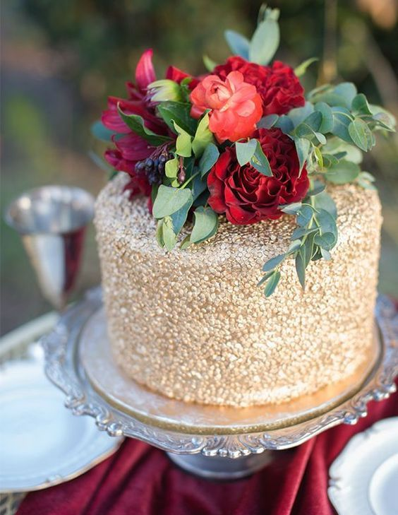gold wedding cake with bold red roses on top