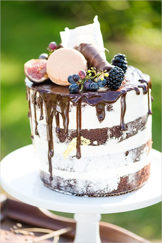 chocolate cake with chocolate drip, topped with grapes, blackberries, figs, macarons