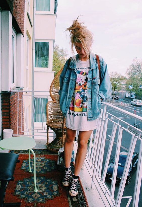 an oversized bold print t-shirt, a denim jacket, black Converse for a 90s inspired look