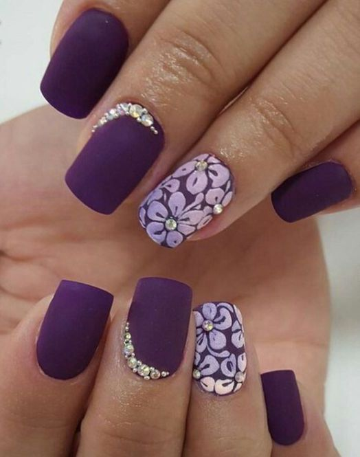 matte deep purple nails with rhinestones accents and floral designs
