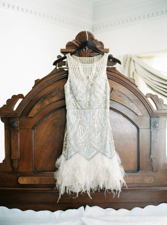 short sleeveless wedding dress with silver embroidery and a feather border on the skirt