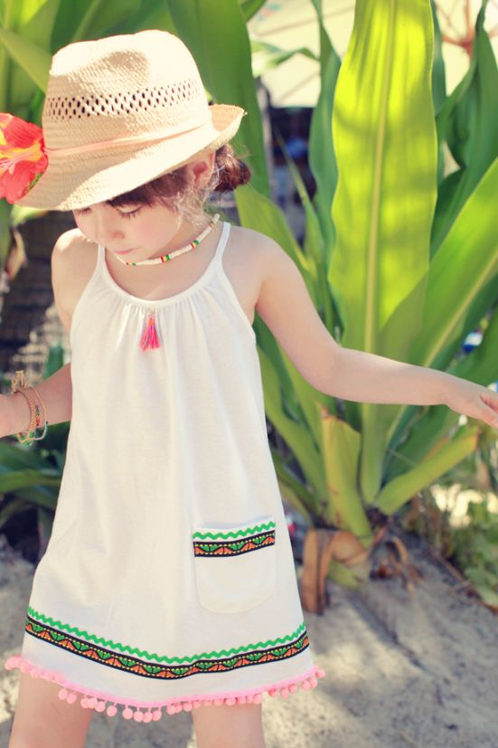 neutral dress with spaghetti straps, printed edge and a pocket and a pompom trim