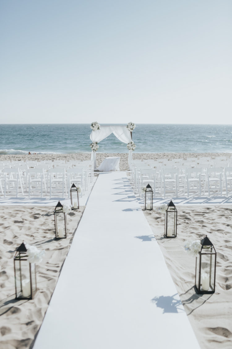The wedding ceremony space was decorated with white chairs, a white fabric arch with white florals and a white aisle runner