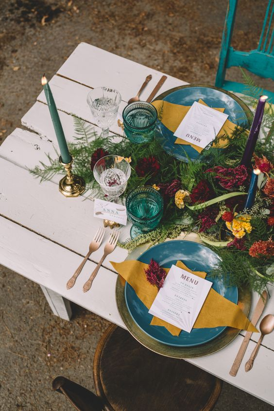 a jewel tone weding table setting with teal and mustard touches