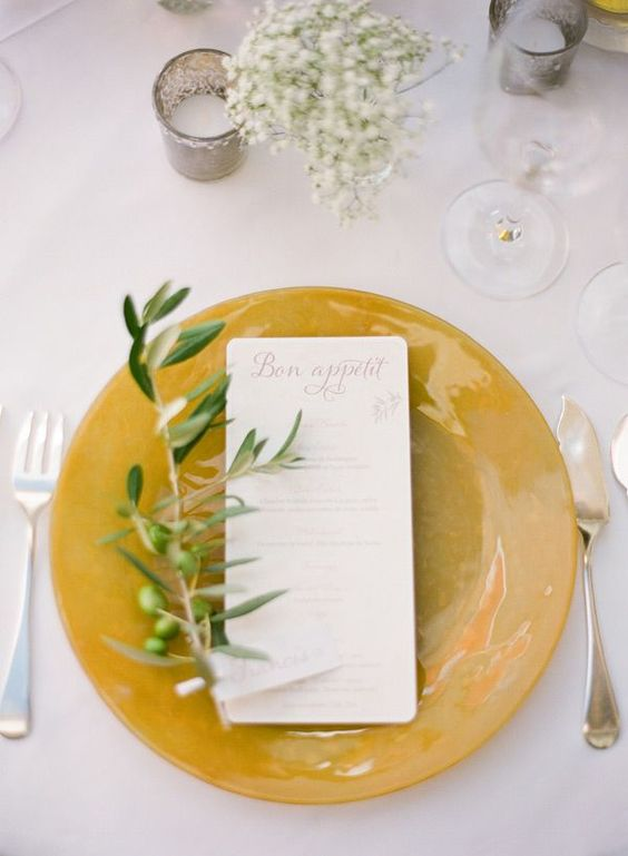 a mustard charger with an olive branch and baby's breath for a fall tablescape