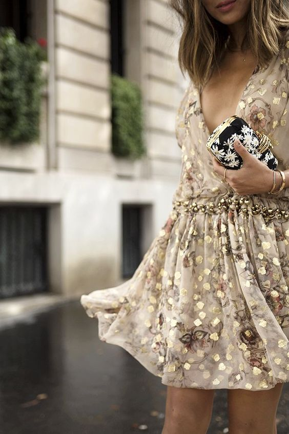 sparkling short gold dress with a deep V-neckline and a floral clutch
