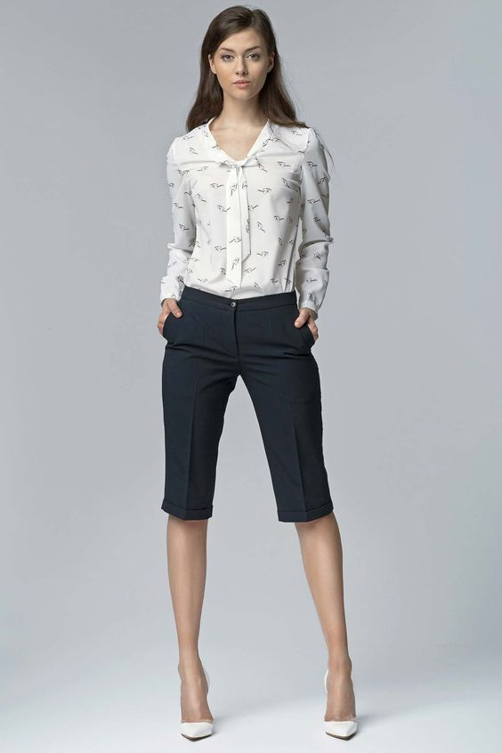 black bermuda shorts, a printed blouse and white pumps for a polished look