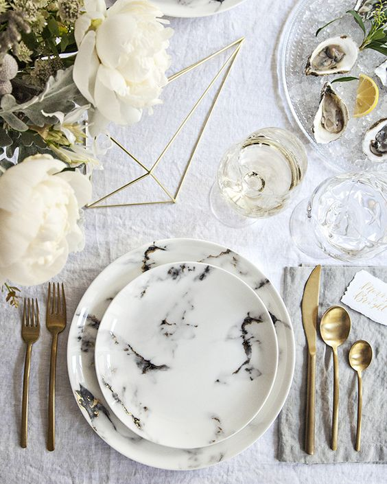 neutral wedding tablescape with gold flatware, neutral florals and marble plates and a charger