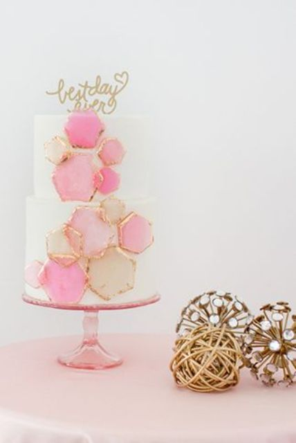 a wedding cake decorated with pink honeycombs with a gilded edge
