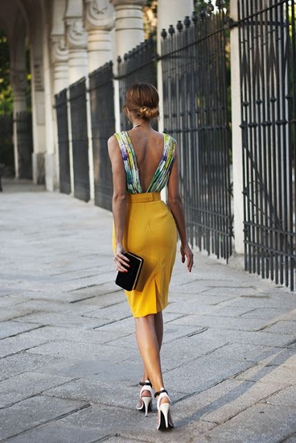 a yellow pencil knee skirt and a colorful printed top with a V back, heels and a clutch