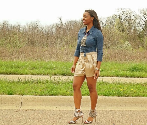 With denim shirt, metallic heels and statement necklace