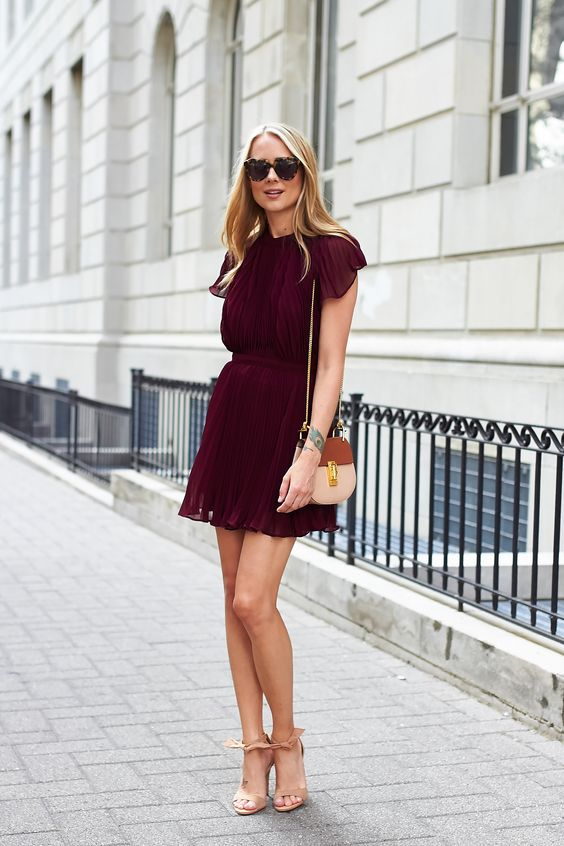 a burgundy pleated mini dress with cap sleeves and neutral heels with ankle straps