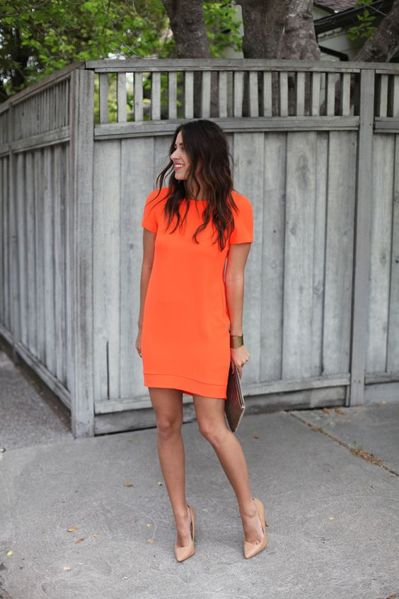 a bold orange mini dress with short sleeves and nude heels