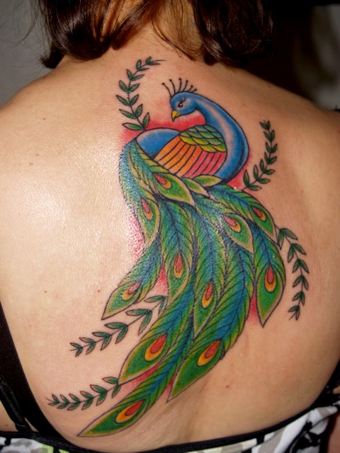 Blue, green and red tattoo on the back