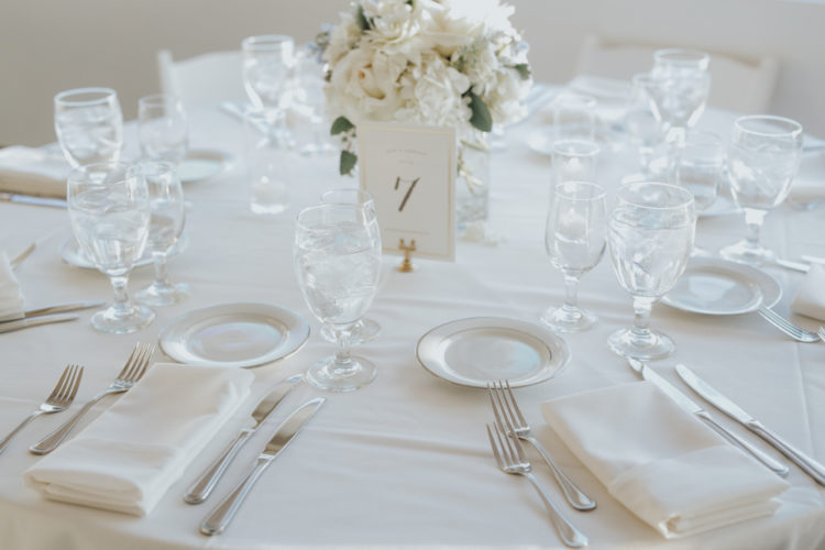 Simple and elegant table decor with white florals, dishes and fabrics