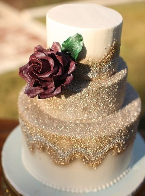 a gold glitter wedding cake with a cream burgundy rose