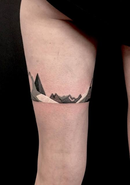 Black, gray and white tattoo on the leg