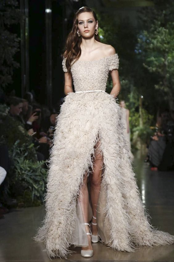 beautiful ostric feather off the shoulder blush wedding dress witih a high front slit and a sparkling bodice
