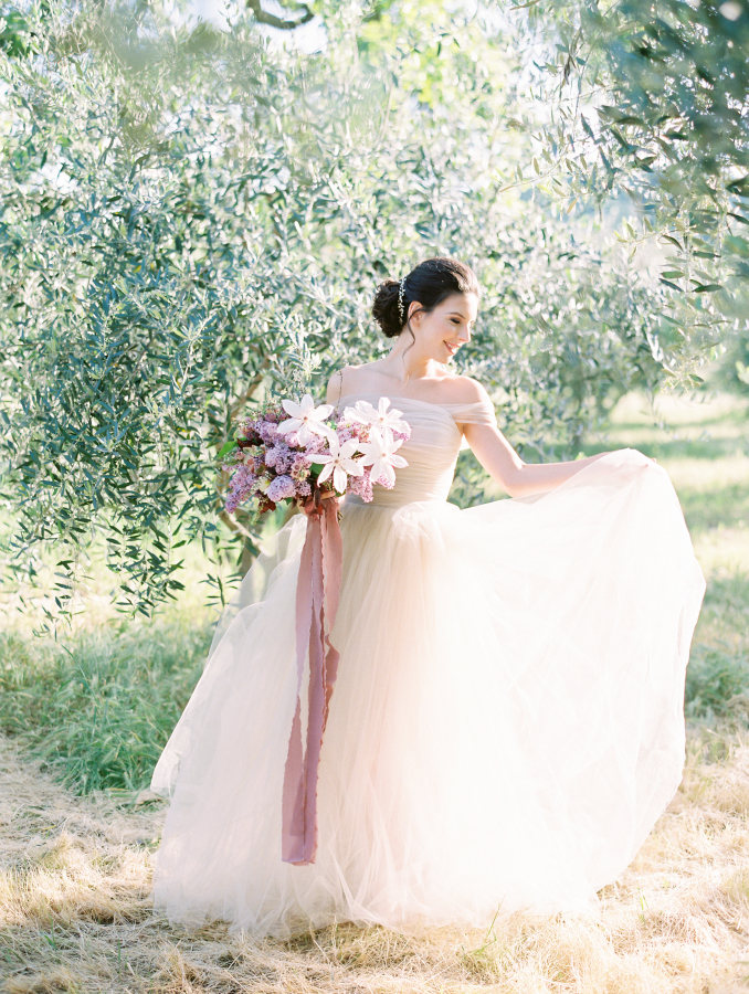 The ethereal off the shoulder blush wedding dress was by BHLDN