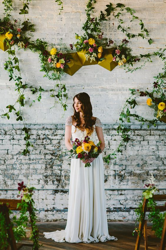 a mustard faceted geometric backdrop with matching florals and a bridal bouquet with the same blooms