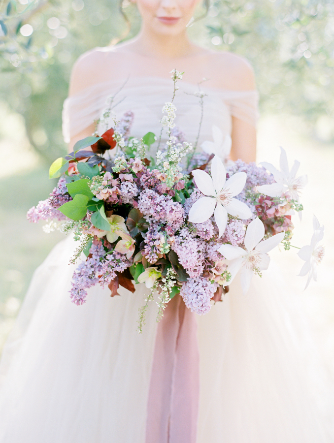 The wedding bouquet contained much lilac and leaves, and a mauve ribbon highlighted it