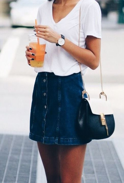 a denim mini skirt with a button row and a white V-neckline t-shirt