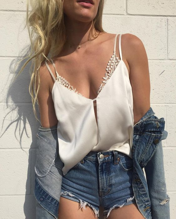 a white lace bralette, a white top, denim shorts and a jacket