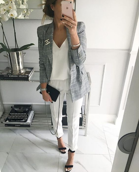 white trousers, a white V-neck top, ankle strap heeled sandals and a grey jacket