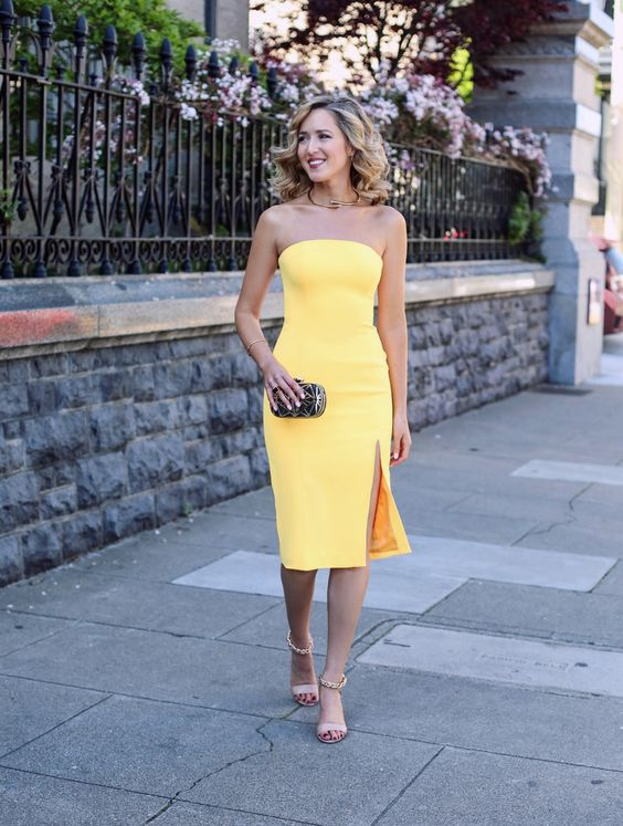 strapless yellow knee dress with a side slit and nude ankle strap shoes