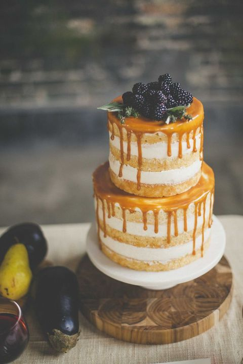 naked wedding cake with salted caramel drip and topped with blackberries