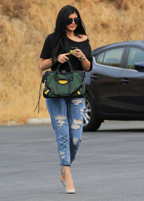 an oversized black tee, ripped boyfriend jeans, grey heels and a green bag