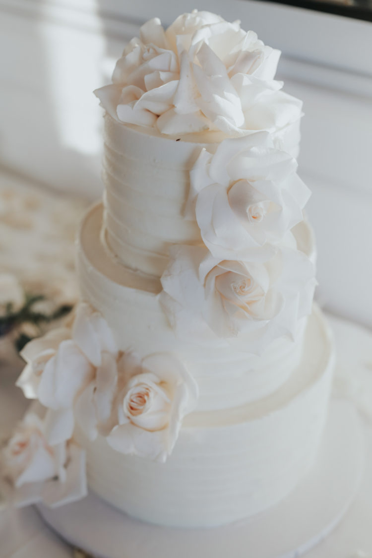 All-white wedding cake decorated with roses was a perfect fit for the wedding