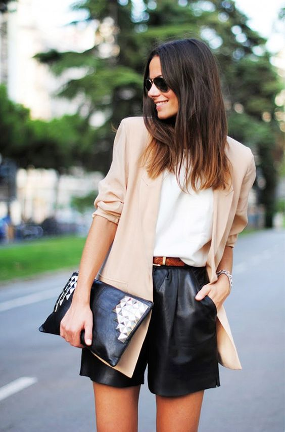 black leather shorts, a white top, a beige blazer and a studded clutch