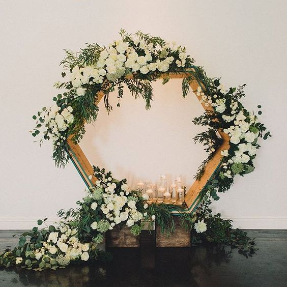 oversized hexagon wedding backdrop with lush greenery, candles and white blooms