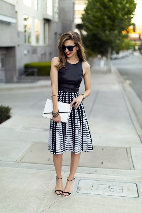 a black halter top, a black and white printed midi skirt and black suede sandals