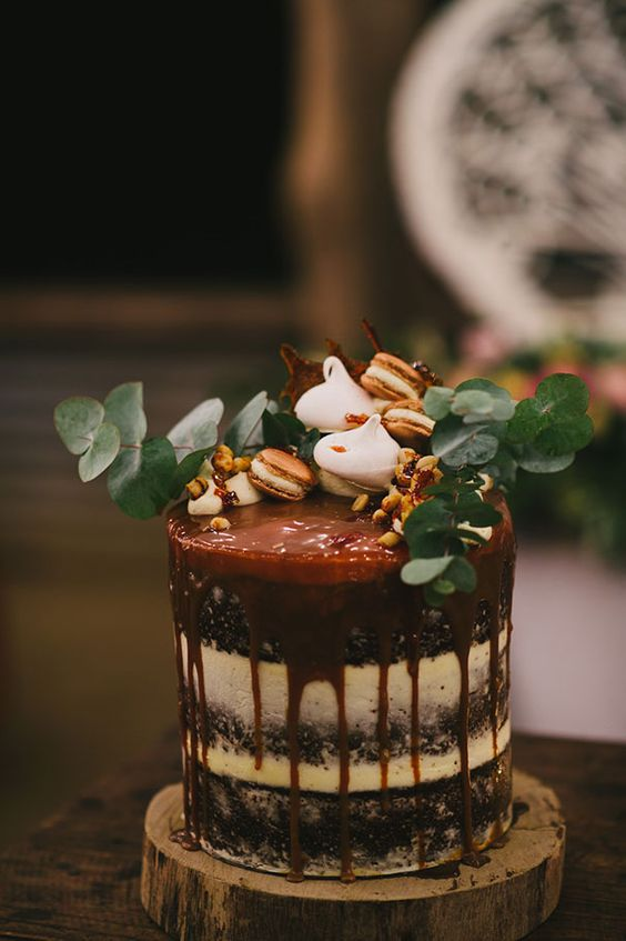 semi naked wedding cake with caramel drip, topped with eucalyptus, macarons and meringues